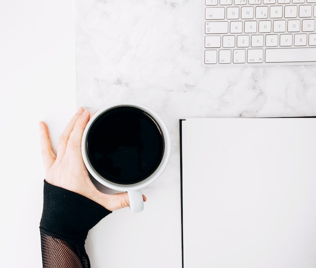 机の上の日記とキーボードとブラックコーヒーカップを持っている人の手のクローズアップ 無料写真
