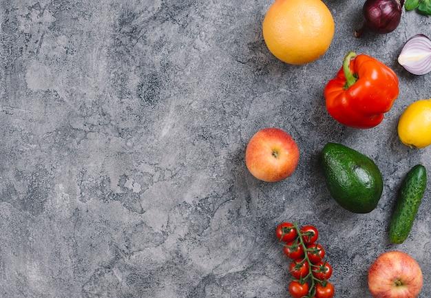 アボカド;トウガラシ属;オレンジ;林檎;きゅうり;コンクリートのテクスチャ背景にレモンとチェリートマト 無料写真