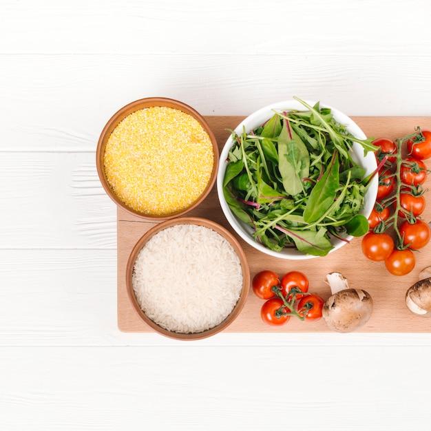 ポレンタのボウル。米粒スイスフダンソウ。白い板の上のまな板にキノコとチェリートマト 無料写真