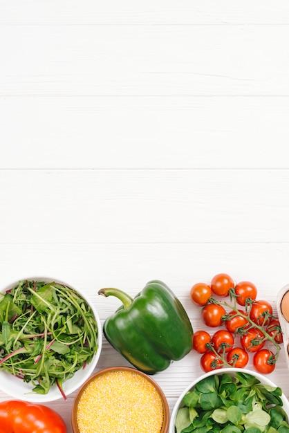 ポレンタと白い木製の机の上の緑豊かな野菜のボウル 無料写真