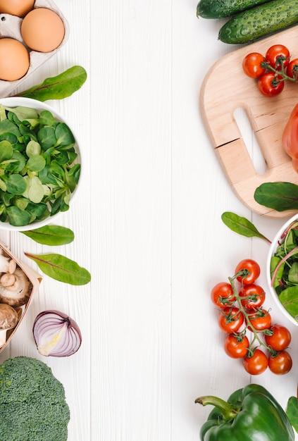 白い木製の机の上にテキストを書くためのスペースと緑豊かな野菜 無料写真