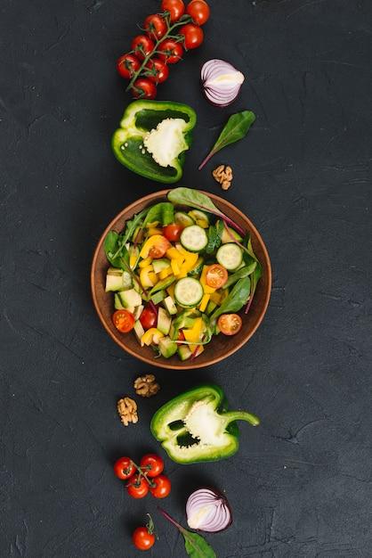 黒キッチンカウンターにカラフルな野菜のサラダ 無料写真