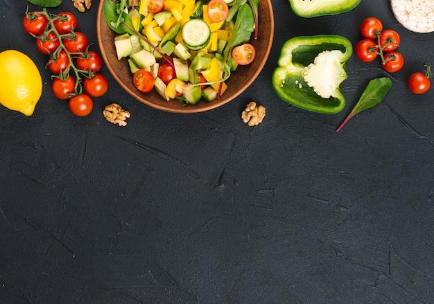 黒いキッチンカウンターに新鮮な健康野菜のサラダの高架ビュー 無料写真