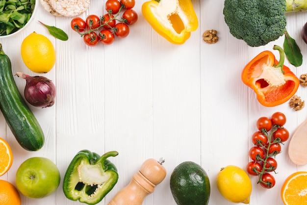 新鮮なカラフルな野菜白い木製の机の上の果物とコショウのシェーカー 無料写真