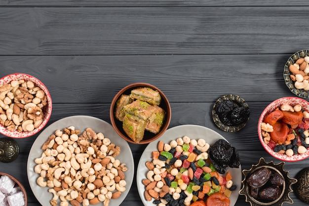 Традиционная арабская рамадан пахлава; сухофрукты и орехи подаются на деревянном столе Бесплатные Фотографии
