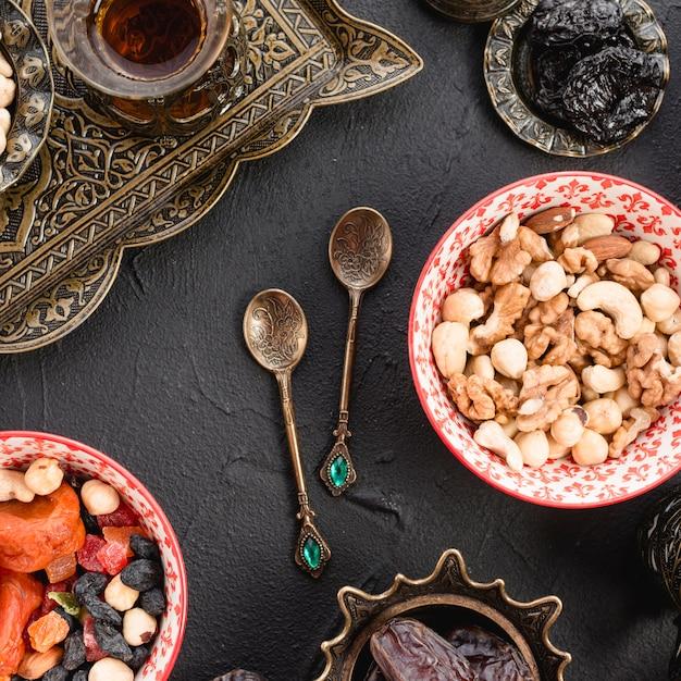 Смесь орехов; чай; сухофрукты и металлические ложки на черном бетонном фоне Бесплатные Фотографии
