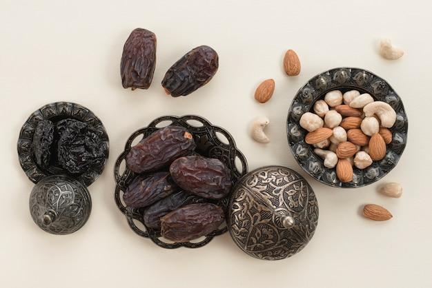 プレミアム日付とナッツの白い背景の上のラマダンカリーム 無料写真