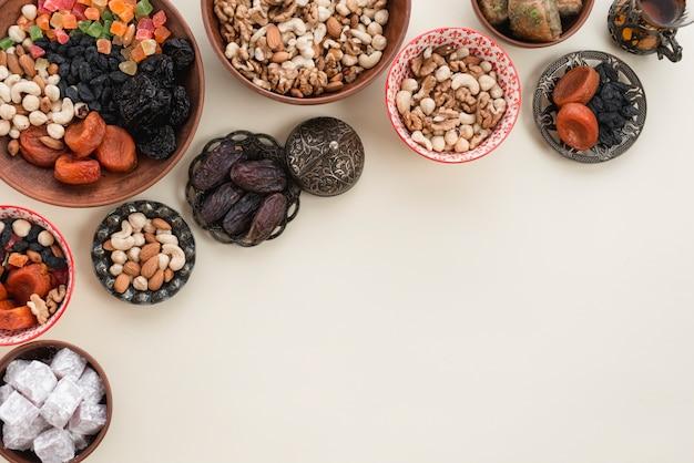 Праздничный натюрморт с восточными рамадан сухофруктами; орехи; даты и лукум на белом фоне Бесплатные Фотографии