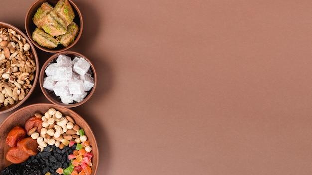 Земляные чаши с орехами; сухофрукты; лукум и пахлава на коричневом фоне Бесплатные Фотографии