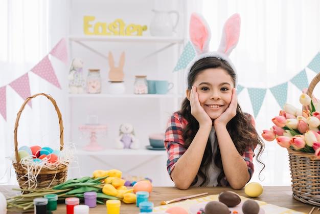 イースターエッグを持つ少女の肖像画。テーブルの上のペンキとチューリップの花 無料写真