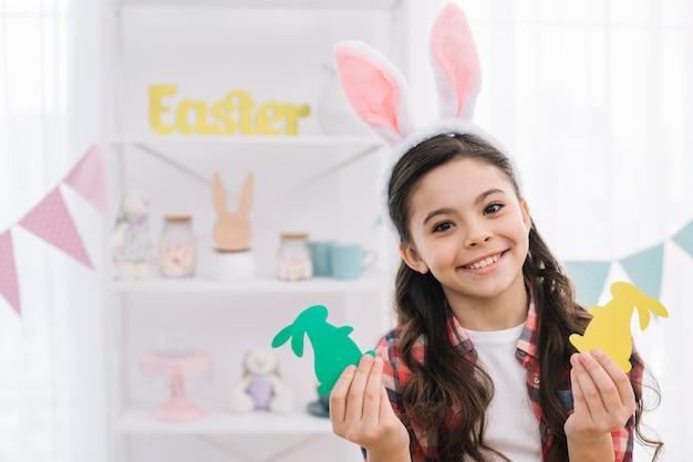 緑と黄色の紙カットアウトイースターを保持している白いバニーの耳を着ている少女 無料写真