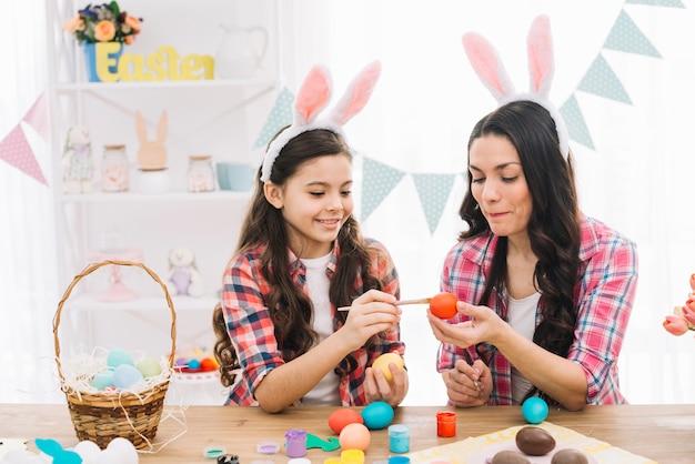 自宅でイースターエッグを塗るための彼女の娘を助ける母 無料写真