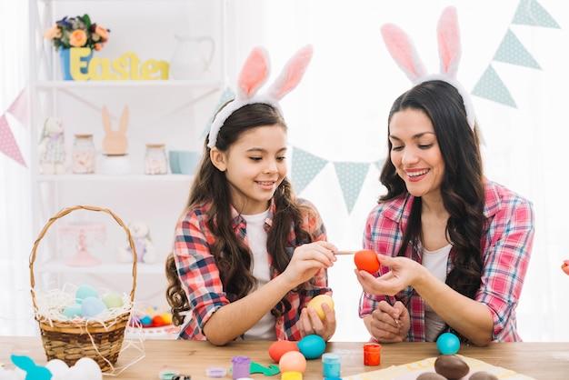 女の子と母親の自宅でイースターの卵を着色のクローズアップ 無料写真