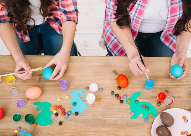 母と娘の木製のテーブルの上にイースターエッグを塗るの俯瞰 無料写真