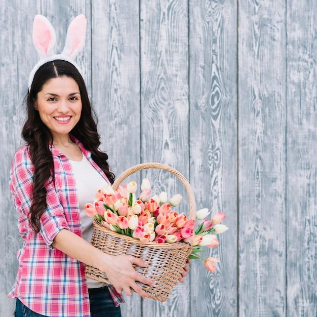 灰色の木製の背景に対してピンクのチューリップバスケットのバスケットを持って笑顔の女性 無料写真