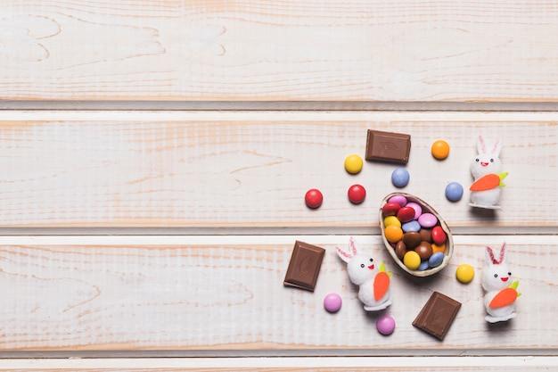 卵の殻に色とりどりの宝石キャンディー。宝石ウサギと木の表面にチョコレートの部分 無料写真