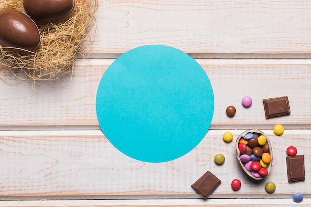 木製の机の上の巣にチョコレートとイースターエッグの青い円形フレーム 無料写真