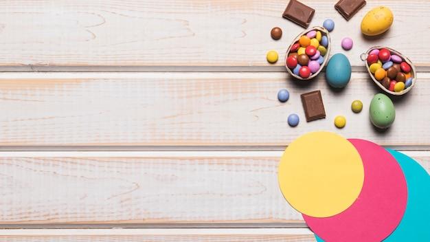 ペーパーサークルデザイン。カラフルなイースターエッグと木製の机の上の宝石キャンディー 無料写真
