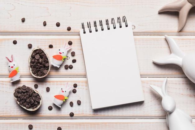 空白のスパイラルメモ帳。チョコチップと木製の背景にウサギとイースターエッグ 無料写真