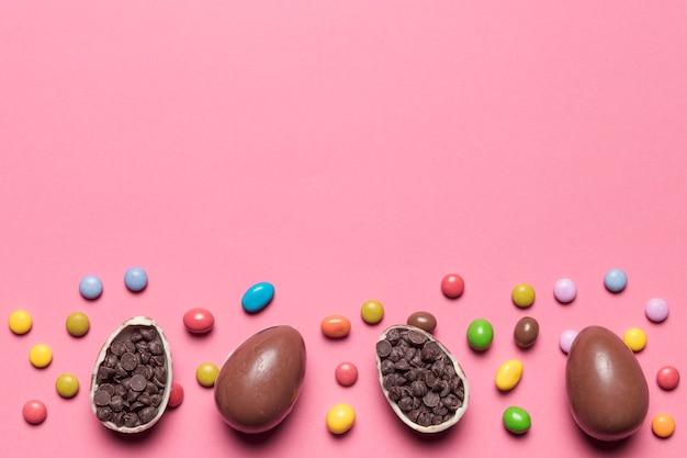 宝石キャンディー。ピンクの背景にチョコチップでいっぱいのチョコレートのイースターエッグ 無料写真