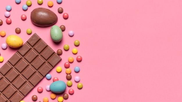 Плитка шоколада; пасхальные яйца и драгоценные конфеты на розовом фоне Бесплатные Фотографии