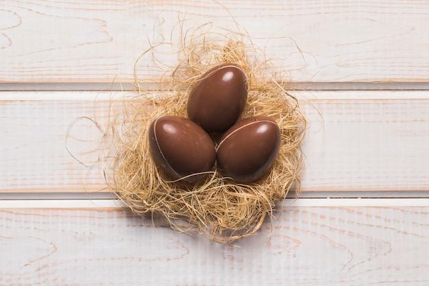 木製の机の上の巣で全体のチョコレートのイースターエッグの立面図 無料写真