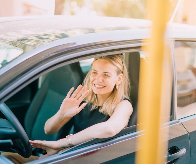 彼女の手を振って車を運転して笑顔の金髪の若い女性 無料写真