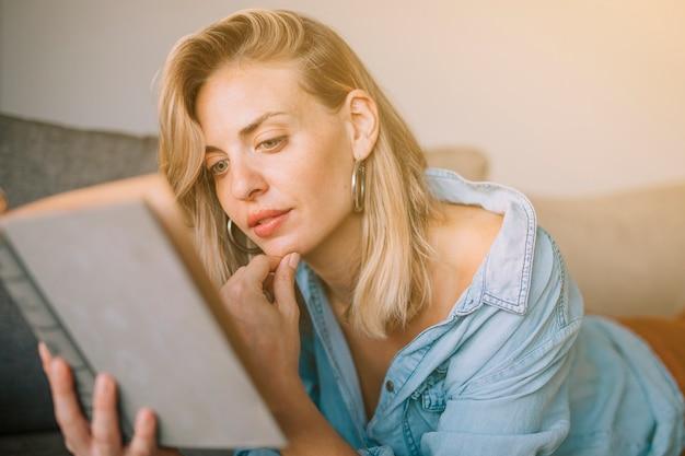 Крупным планом блондинка с рукой на подбородке, читая книгу Бесплатные Фотографии