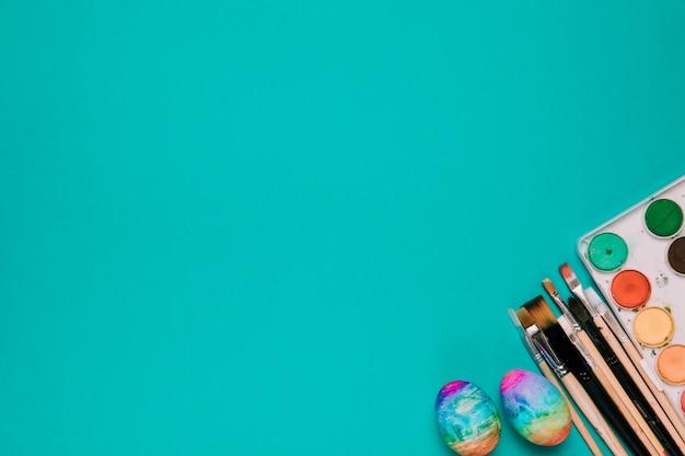 Крашеные пасхальные яйца; кисти и акварельные краски на углу зеленого фона Бесплатные Фотографии