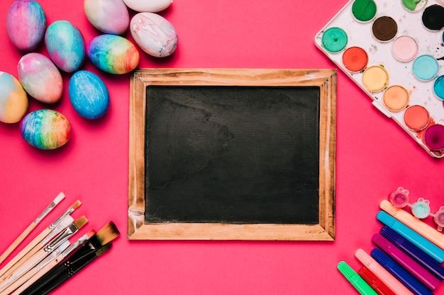 イースターエッグに囲まれた木製の黒板。ペイントブラシ;ピンクの背景にフェルトペンと水カラーペイントボックス 無料写真