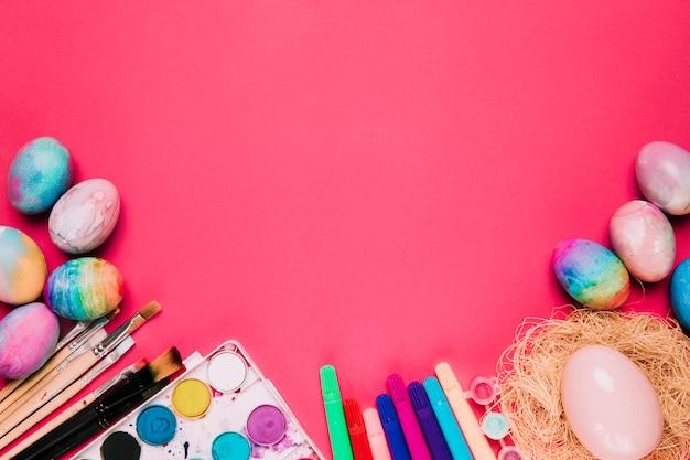 塗装水彩画イースターエッグの俯瞰。ペイントブラシ;ピンクの背景にフェルトペンとイースターエッグ 無料写真