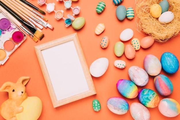 カラフルなイースターエッグと空の白い枠。ペイントブラシ;オレンジ色の背景上の水彩画とウサギの像 無料写真