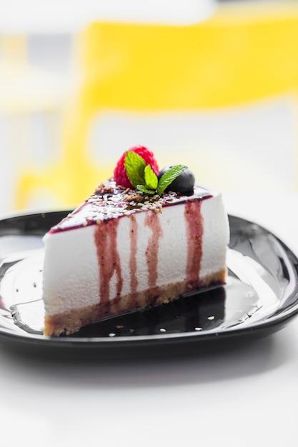 ラズベリーをトッピングしたソフトケーキ。ミント;ぼかしを背景にブラックプレートにブルーベリー&チョコレートソース添え 無料写真