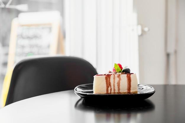 木製のテーブルの上の黒い皿にブルーベリーのチーズケーキ 無料写真