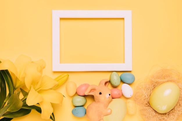 ユリの花で飾られた空の白い枠。黄色の背景にウサギの置物とイースターエッグ 無料写真
