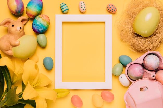 イースターエッグで飾られた空の白い枠。ユリの花と黄色の背景に巣 無料写真