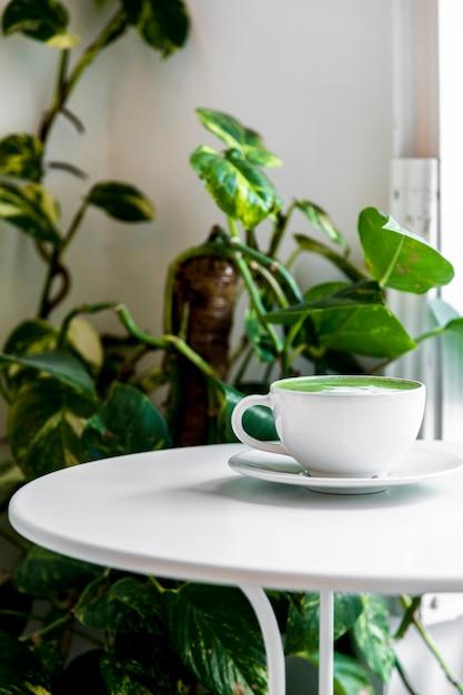 白いテーブルの上のカップに熱いお茶抹茶ラテ 無料写真