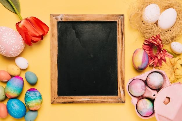 Пустой доске со свежими цветами и украшенные пасхальные яйца на желтом фоне Бесплатные Фотографии