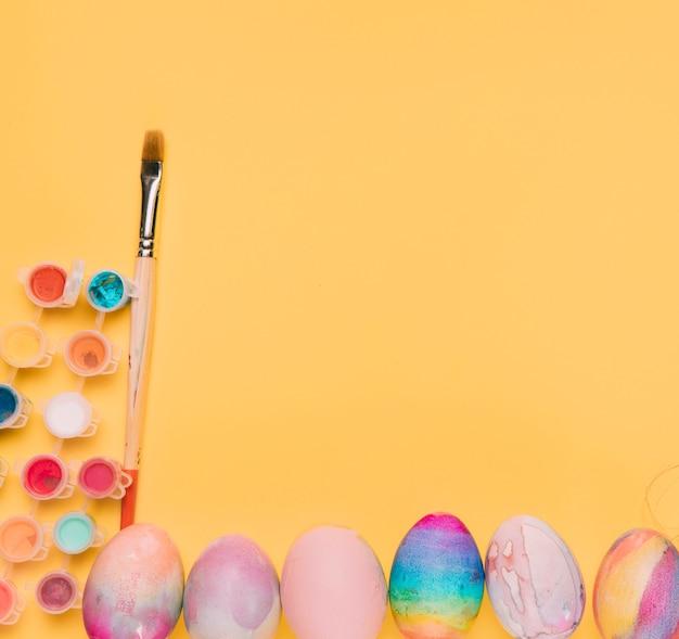 Красочные акварельные краски с кистью и пасхальные яйца на желтом фоне с пространством для написания текста Бесплатные Фотографии