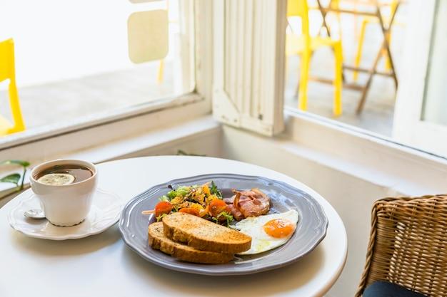ティーカップ窓の近くのテーブルに健康的な新鮮な朝食 無料写真