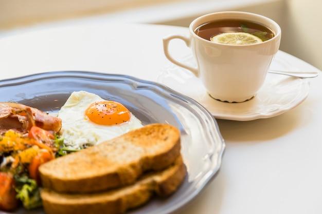 健康的な朝食と白いテーブルの上のティーカップ 無料写真