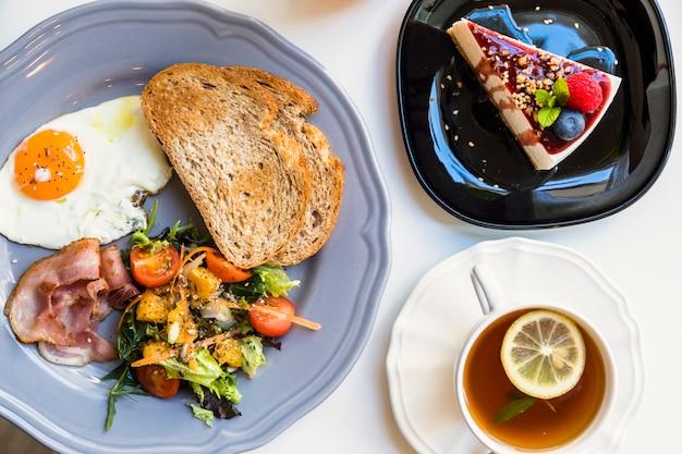 Поднятый вид вкусного чизкейка; чашка чая с лимоном; тост; салат; жареные яйца и бекон на серой тарелке на белом фоне Бесплатные Фотографии