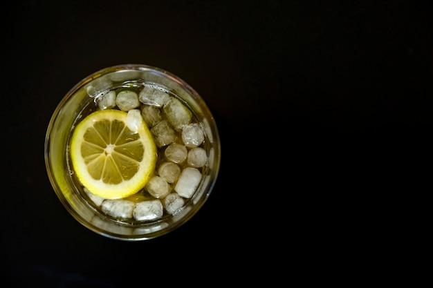 黒の背景上のレモンスライスと冷たいアイスティーグラス 無料写真