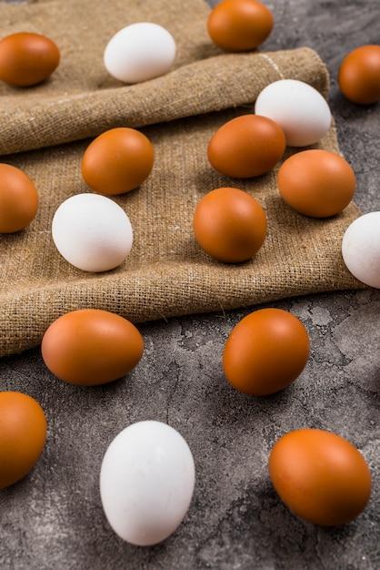灰色のテーブルの上のキャンバスに散在している鶏の卵 無料写真