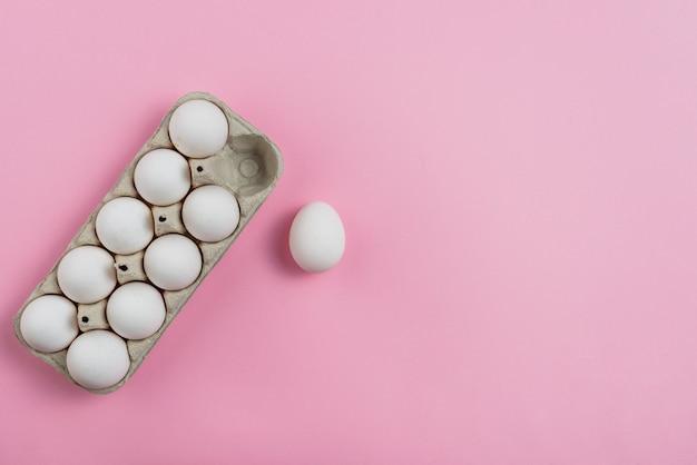 ピンクのテーブルの上のラックに白い鶏の卵 無料写真
