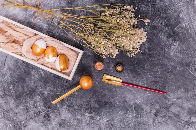 ペイントブラシと花の金のイースターエッグ 無料写真