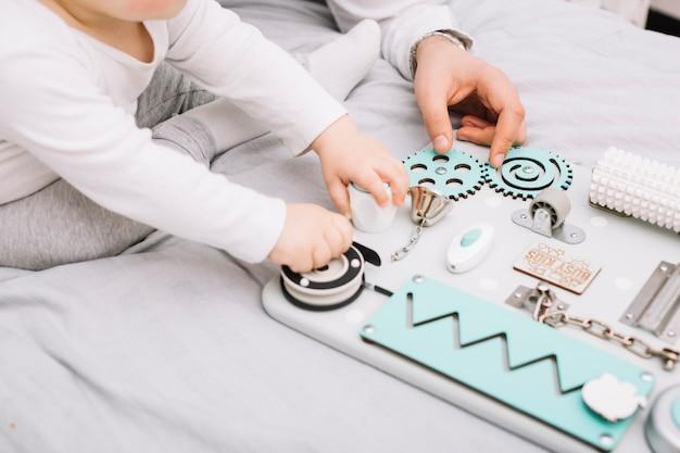 Человек возле маленького ребенка с игрушкой, сидя на кровати Бесплатные Фотографии