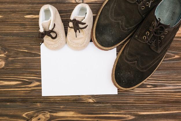 男性と子供の靴の近くの紙 無料写真