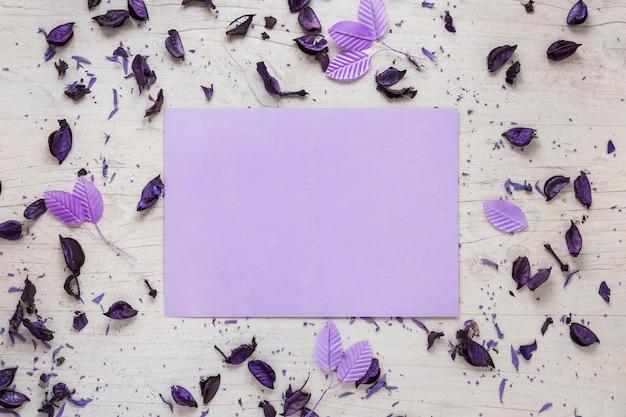 Чистый лист бумаги с лепестками цветов и листьев на столе Бесплатные Фотографии