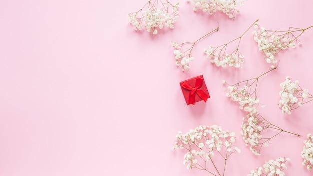 テーブルの上の花の枝を持つ小さなギフトボックス 無料写真